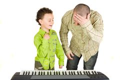 Kid playing piano badly. Schoolboy playing badly at the piano while the teacher shows disappointment Stock Images