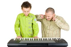 Kid playing piano badly. Schoolboy playing badly at the piano while the teacher shows disappointment Stock Photo