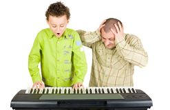 Kid playing piano badly. Schoolboy playing badly at the piano while the teacher shows disappointment Stock Photos