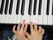 Kid playing piano, close up of keyboard and hands Stock Photography