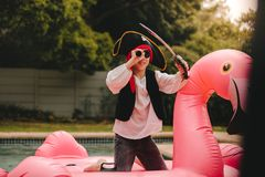 Kid playing pirate on inflatable mattress in pool stock images