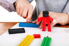 Kid playing with Plasticine Closeup Stock Photo