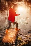 Kid playing in puddle in sunset Stock Photo