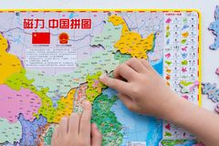 Kid playing puzzle map of China and putting the Beijing into the correct position royalty free stock photo
