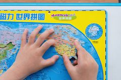 Kid playing puzzle map of the World and putting the US into the correct position. Zhongshan,China-April 15,2018:kid playing puzzle map of the World and putting royalty free stock photography