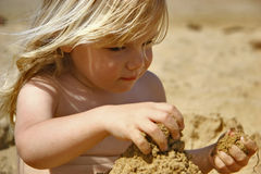 Kid playing in sand. A cute female toddler playing in the sand at the beach Royalty Free Stock Photos