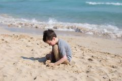 Kid playing with sand on the beach alone. Little boy near sea. Summer play stock photo