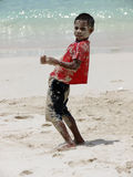 Kid playing with sand. Andamanese kid playing with sand on the beach. Face and clothes covered with sand. Looking at camera, Andaman and Nicobar Islands, India Stock Photo
