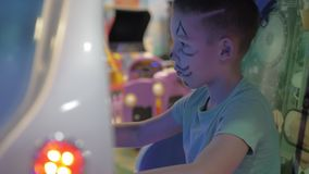 Kid playing sea-battle simulator in amusement park. Boy in amusement park. Child is attracted with sea-battle video game simulator stock video footage