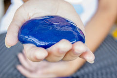 Kid playing slime. Kid playing blue slime in her hands stock photo