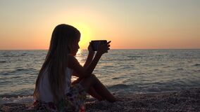 Kid Playing Smartphone, Child on Beach at Sunset, Young Blonde Girl Using Tablet on Seashore at Sundown in Summer Vacation