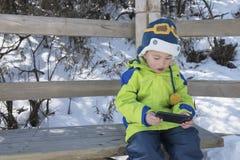 Kid playing smartphone Stock Image