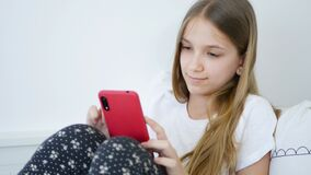 Kid Playing Smartphone at Home, Teenager Girl Browsing Internet in Bedroom, Child in Bed use Touchscreen Gadgets
