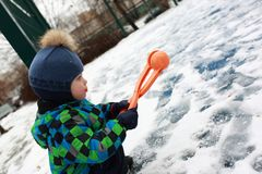 Kid playing with snowball maker Stock Photography