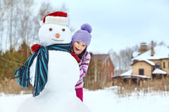 Kid playing with snowman Royalty Free Stock Photo