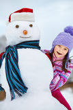 Kid playing with snowman Stock Photos