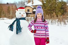 Kid playing with snowman Royalty Free Stock Photography