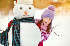 Kid playing with snowman. Happy kid playing with snowman. funny little girl on a walk in the winter outdoors Stock Image