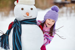 Kid playing with snowman Royalty Free Stock Photos