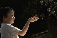 Kid playing with soap bubbles. Kid playing with soap bubbles in the backyard Royalty Free Stock Photography