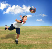 Kid playing soccer outside stock image