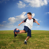 Kid playing soccer outside royalty free stock image