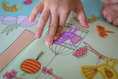Kid playing stickers : bird. Activity bird book cage child Closeup day finger girl hand high angle view holiday imprison indoor kid learning People stick stock photo