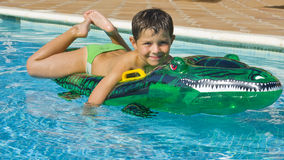 Kid playing at the swimming pool Stock Images
