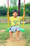 Kid playing with swing. Kid in India playing with swing in evening time royalty free stock images