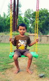 Kid playing with swing. Kid in India playing with swing in evening time stock photo