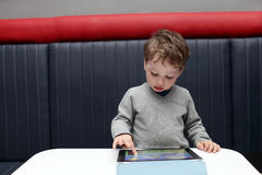 Kid playing with tablet PC Stock Image