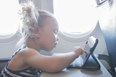 Kid playing with tablet in plane. Royalty Free Stock Photography