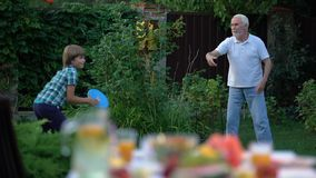 Kid playing throw and catch game with grandfather, active lifestyle, having fun