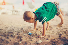 Kid playing with toy cars sitting outdoors at pebble beach Stock Images