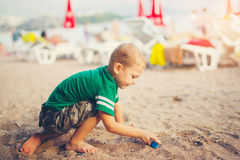 Kid playing with toy cars sitting outdoors at pebble beach Stock Photography