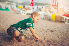 Kid playing with toy cars sitting outdoors at pebble beach Royalty Free Stock Photo