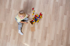 Kid playing with toys on floor top view Stock Images