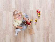 Kid playing with toys on floor top view Royalty Free Stock Image