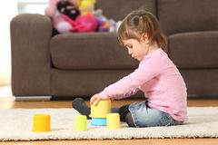Kid playing with toys at home. Side view of a kid playing with toys sitting on the floor of the living room at home Stock Photos