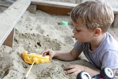 Kid in sandbox. Kid playing with toys in a sandbox Stock Photos