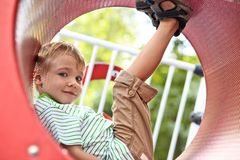 Kid playing in tunnel on playground Stock Photo