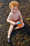 Kid playing in water. Young boy (3) sitting in the water, happy smiling looking up, playing with toy scoop and bucket Stock Image
