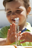 Kid playing with water. Dinking fountain - child playing with water Royalty Free Stock Photography