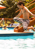 Kid jumping into the pool Stock Image
