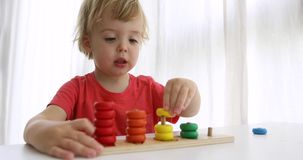 Kid playing with wooden developing puzzle toys stock footage