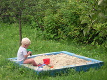 Kid in playpit. On green royalty free stock photography