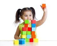 Kid plays with building blocks and shows red cube Stock Photo