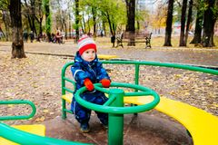 The child is spinning on a swing in the playground in the park. The kid is spinning on a swing in the playground in the park royalty free stock photography