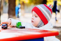 The kid plays cars on the street Royalty Free Stock Images