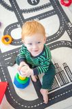 Kid plays developing toys. In the children`s room Royalty Free Stock Images